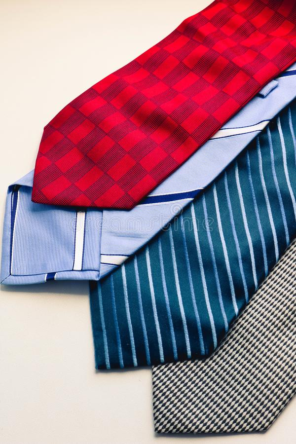 Placez des liens de l'homme multicolore de mode Liens gris et rayés bleus rouges sur le fond blanc photo stock
