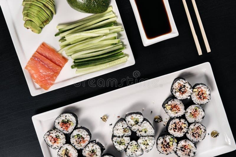 Placez des petits pains avec les poissons et le gingembre rouges Ajournez la configuration Fond noir photo libre de droits