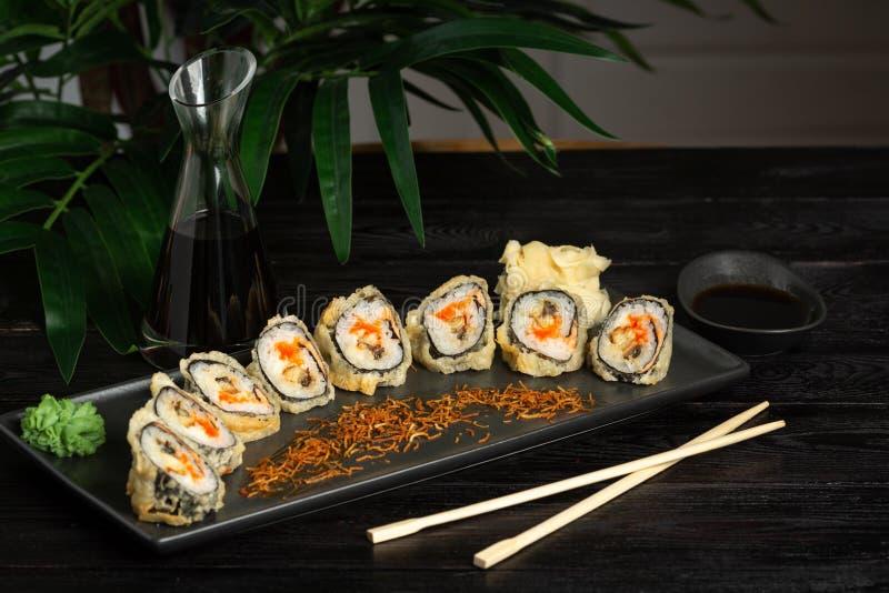 placez des petits pains de sushi d'un plat noir sur un fond en bois noir avec les feuilles vertes d'une plante d'int?rieur images libres de droits