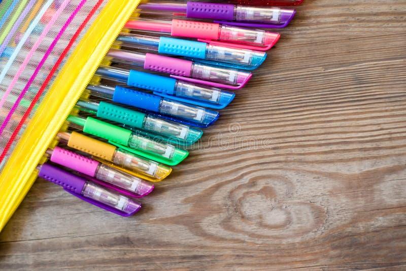 Placez des stylos multicolores de gel sur un fond en bois photos stock