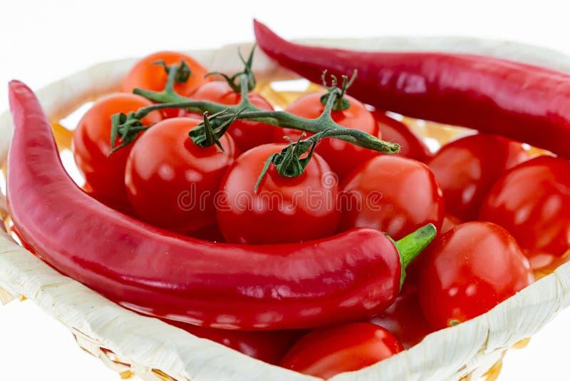 Placez des tomates rouges de légumes juteux sur de longues cosses d'une branche des ingrédients appétissants de sauce chaude à lé image stock