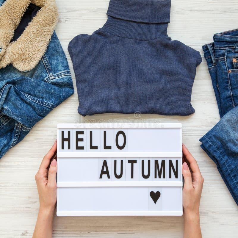 """Placez des vêtements femelles d'automne, mains femelles tenant le lightbox avec """"bonjour des mots d'automne """" Vue a?rienne, d'en  image stock"""