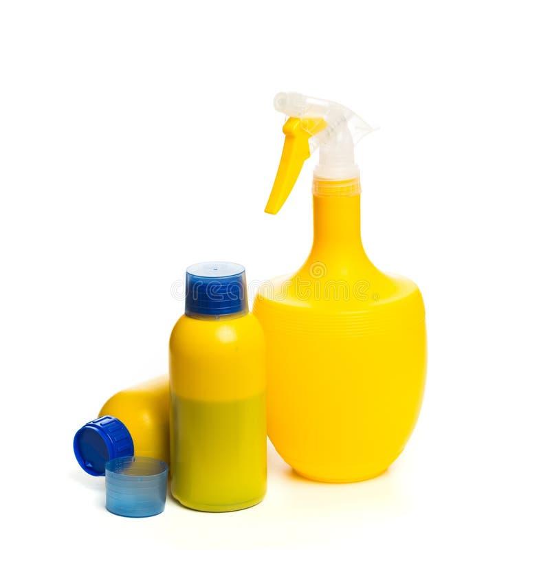 Placez du pulvérisateur et de l'engrais jaunes d'usine pour mûrir dans la bouteille d'isolement sur le fond blanc photographie stock