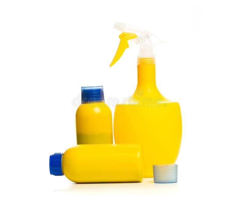 Placez du pulvérisateur et de l'engrais jaunes d'usine pour mûrir dans la bouteille d'isolement sur le fond blanc photos libres de droits