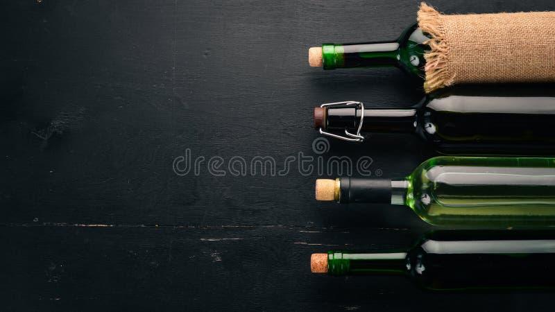 Placez du vin rouge et blanc en bouteilles et verres raisin Sur un fond en bois noir L'espace libre pour le texte image libre de droits