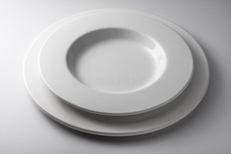 Placez le rond et le plat de cuvette et plat ?pais blanc photo libre de droits