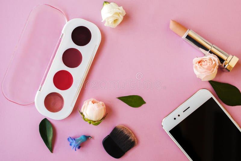 Placez les cosmétiques et le Smartphone, style du ` s de femmes, fond rose photographie stock