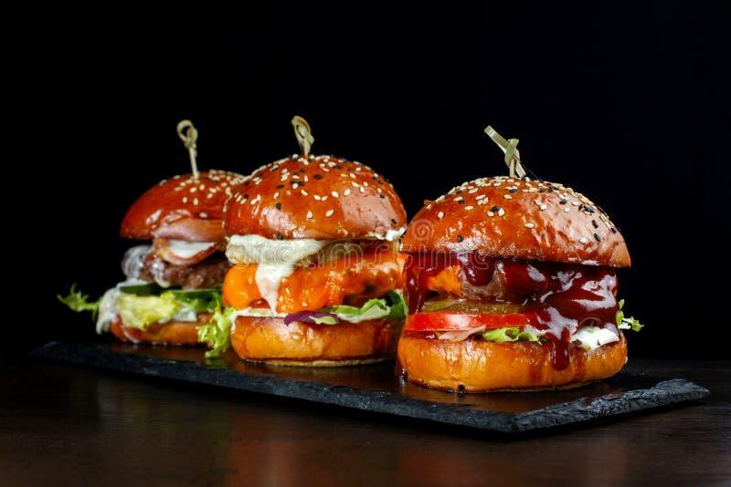 Placez les hamburgers avec du boeuf Sur un fond noir image stock