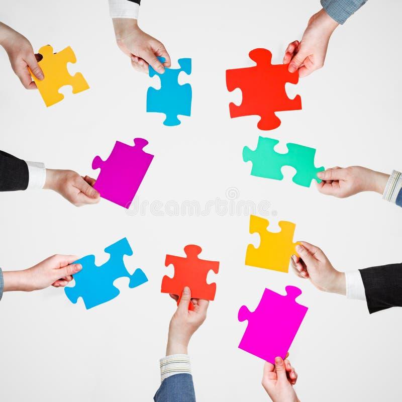 Placez les morceaux de puzzle dans des mains de personnes en cercle images libres de droits