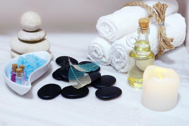 Placez pour des procédures de station thermale sur une table de marbre blanche - huile aromatique, pierres pour le massage chaud, photo stock