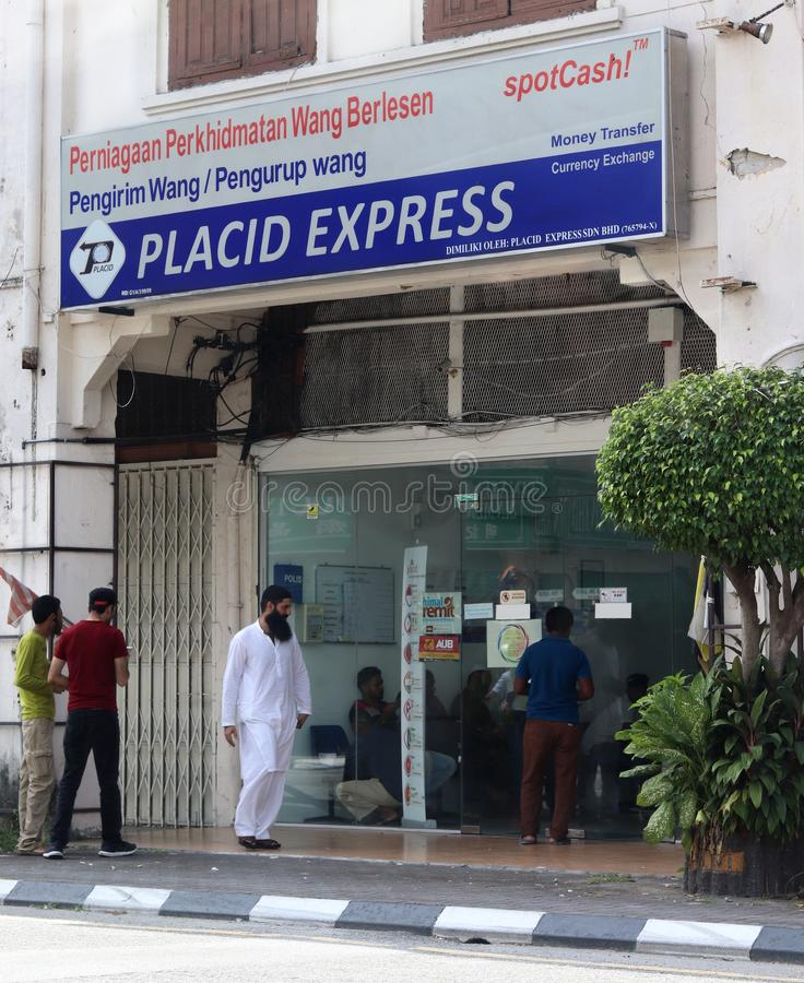 Placid Express Outlet In Malaysia. Migrant workers of various nationality at the Placid Express outlet in Ipoh, Malaysia. Some can be seen waiting inside to royalty free stock photos