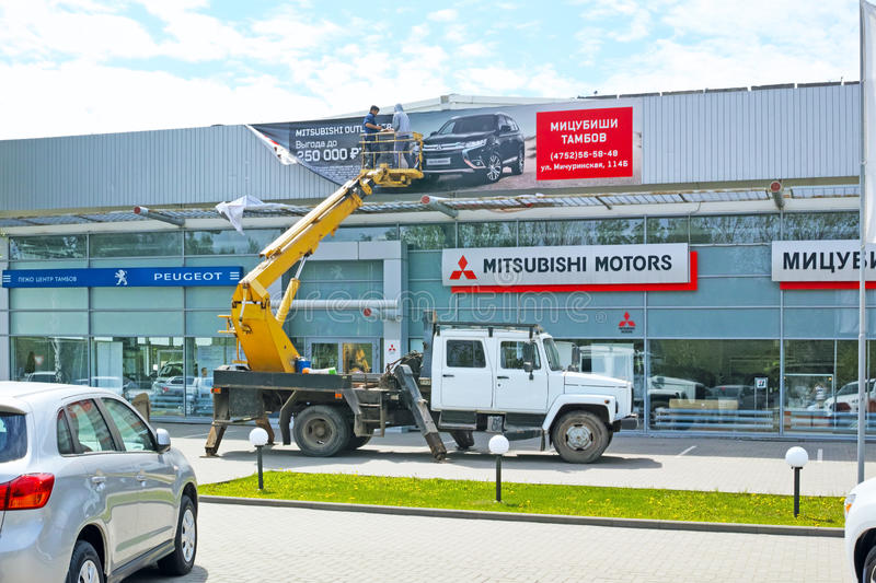 Placing a banner on the Mitsubishi motors. Tambov, Russia - May 13, 2015: The works on placing an advertising banner at the salon Mitsubishi Motors in the city royalty free stock photo