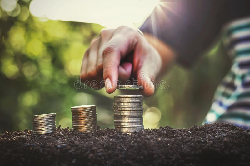 Placing the coin as a step Investment concepts and saving Growing business. Economy, profit, payment, sunset, sunlight, investor, businessman, putting, sunrise stock photography