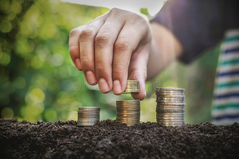 Placing the coin as a step Investment concepts and saving Growing business. Economy, profit, payment, sunset, sunlight, investor, businessman, putting, sunrise royalty free stock image