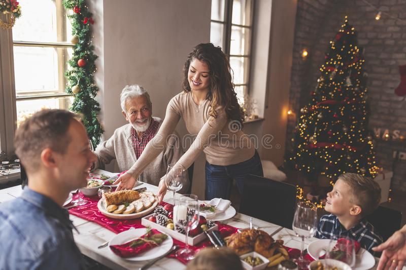 Placing food on the table for family Christmas dinner. Happy family having Christmas dinner all together at home, speaking to each other and laughing while young royalty free stock photos