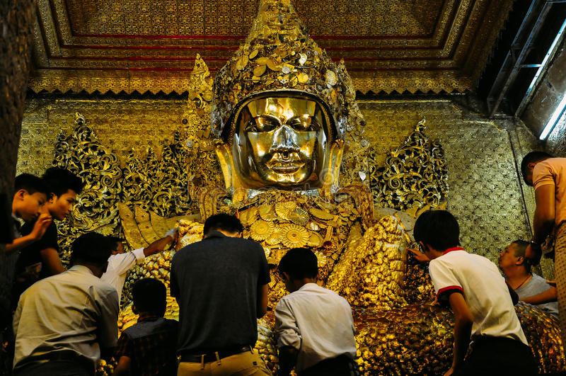 Placing gold leaf on gold statue of Buddha in Mahamuni temple in Mandalay. stock photography