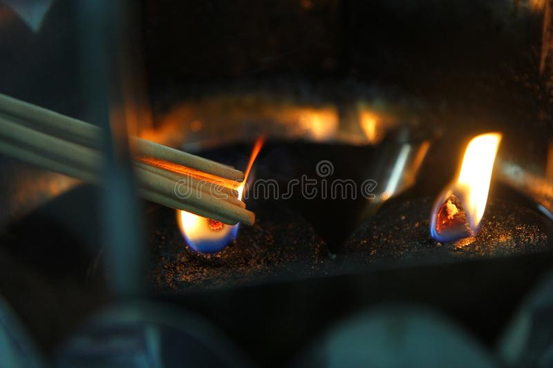 Placing the lit incense with lamp frame for worship Buddha. royalty free stock photo