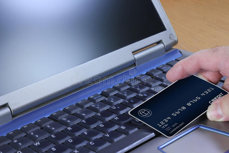 Placing an Order Online. A hand holding a generic credit card at a laptop computer stock photography