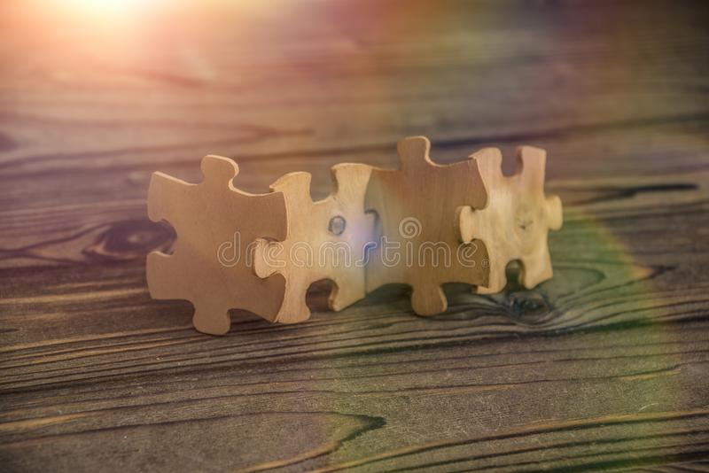 Placing a piece of the puzzle in a row on a textured rustic wooden table. Conceptual work in the team and cooperation royalty free stock image