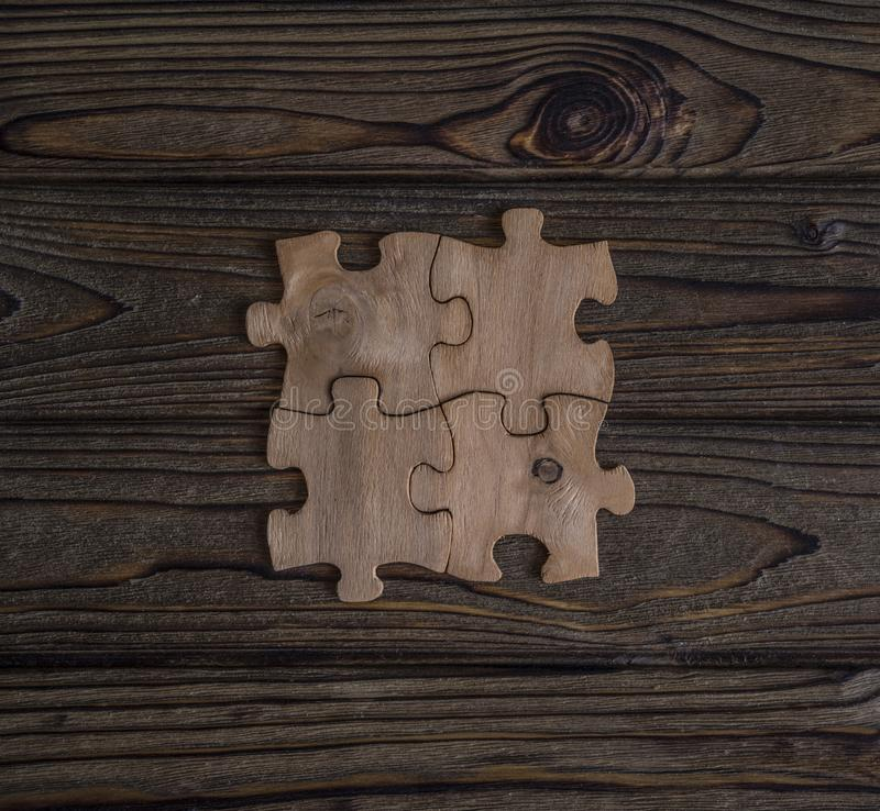 Placing a piece of the puzzle on a textured old wooden table. Conceptual work in the team and cooperation. idea of business royalty free stock photo