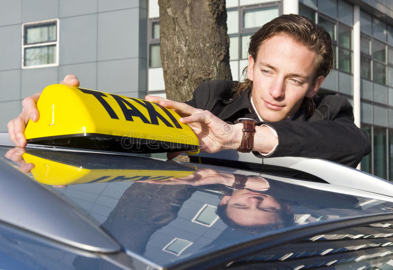 Placing the Taxi sign stock photography