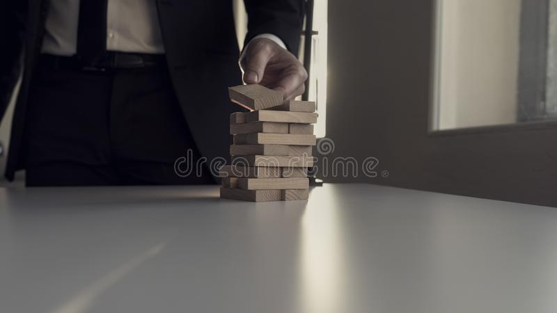 Placing wooden block on tower with a natural sunlight from behind stock image