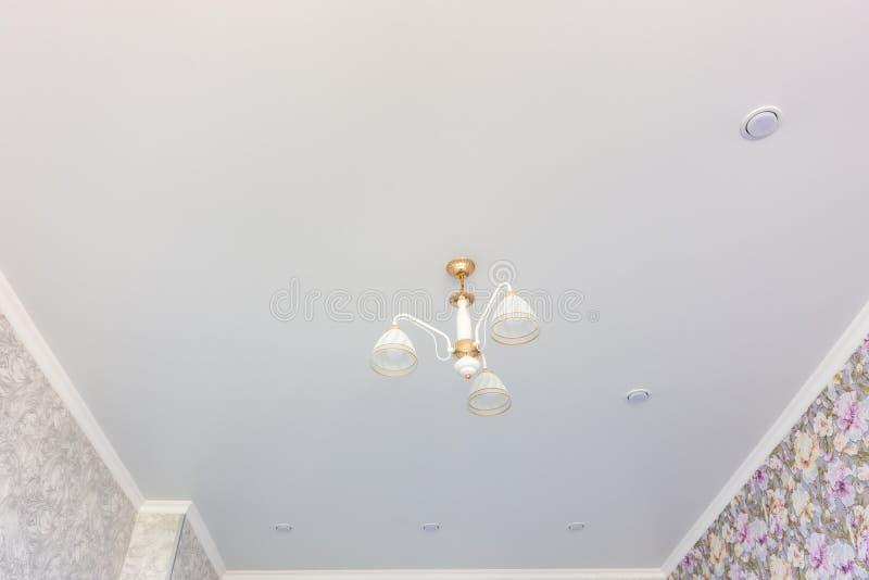 Plafond mat de bout droit dans la chambre avec un lustre et des projecteurs, avec la lumière naturelle photos libres de droits