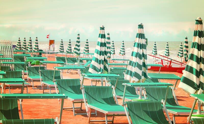 Plage abandonnée avec des lits pliants et des parapluies chez l'Adriati italien image libre de droits