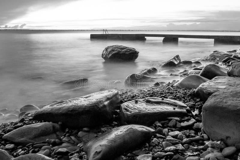 Plage aux vagues et aux roches de tir de nuit photographie stock
