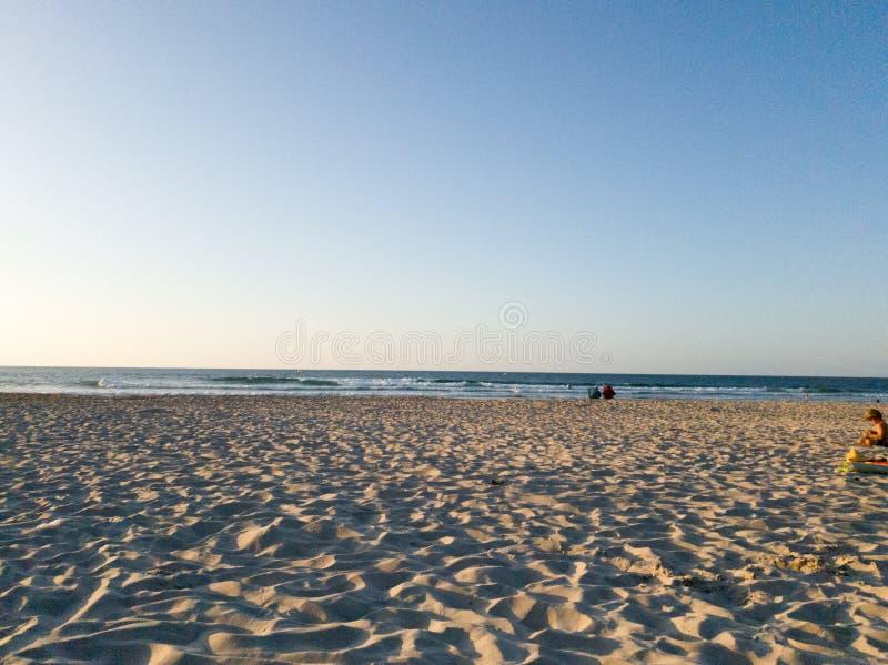 Plage avec deux gros rochers au coucher du soleil photographie stock libre de droits