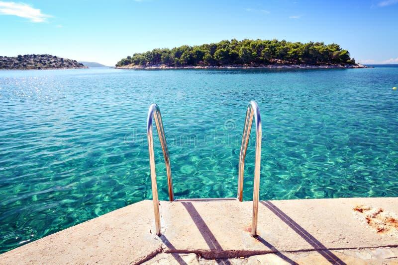 Plage avec l'eau et l'île de mer claires image libre de droits