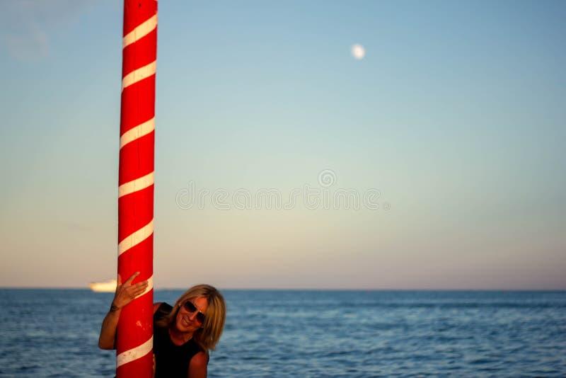 plage avec la femme blonde et un poteau de amarrage rouge Horizontal merveilleux image libre de droits