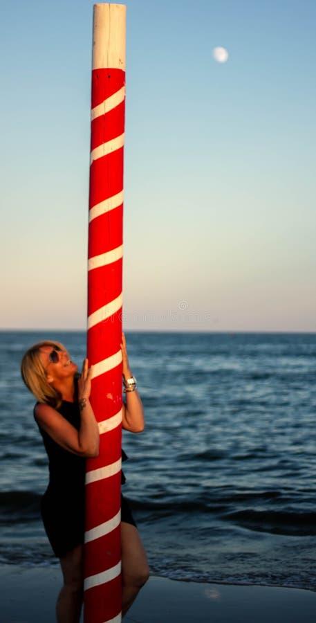 plage avec la femme blonde et un poteau de amarrage rouge Horizontal merveilleux photographie stock libre de droits