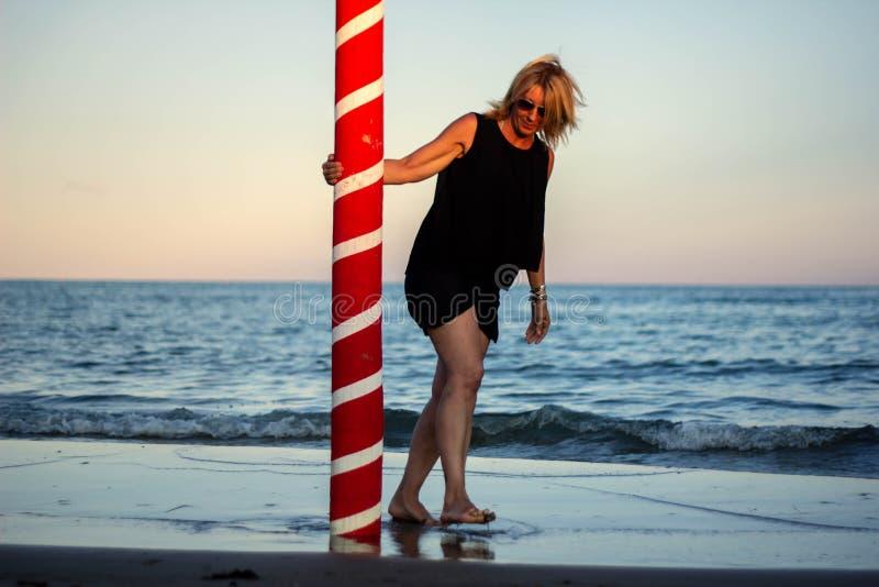 plage avec la femme blonde et un poteau de amarrage rouge Horizontal merveilleux image stock