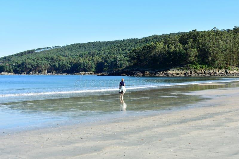 Plage avec la marche humide de sable et de femme de roux Mer bleue avec la mousse, la forêt et les roches Ciel bleu, jour ensolei photo stock