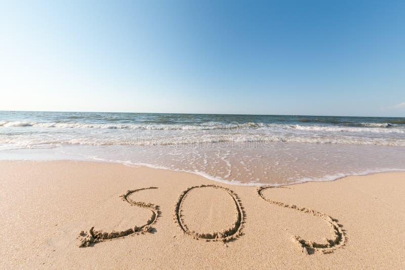 Plage avec le mot SOS de sable photographie stock