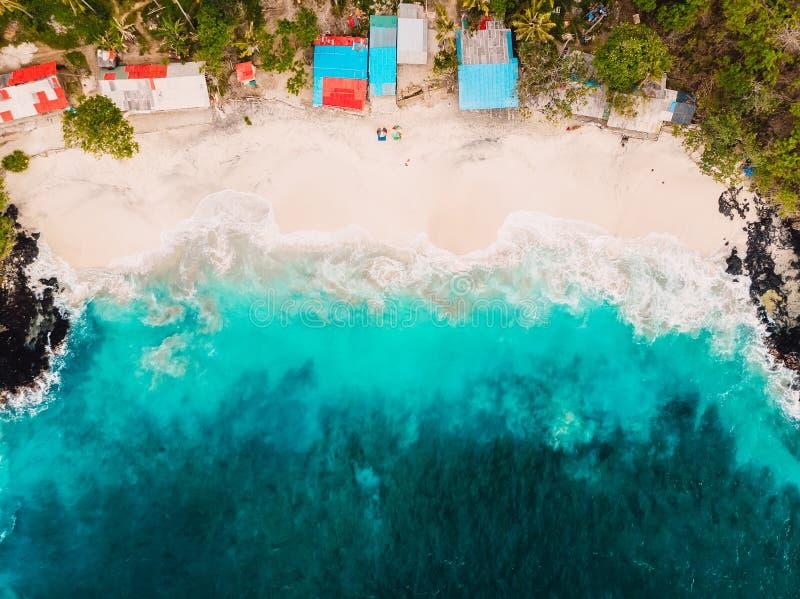 Plage blanche tropicale de sable avec les cocotiers et l'océan de turquoise Silhouette d'homme se recroquevillant d'affaires images stock