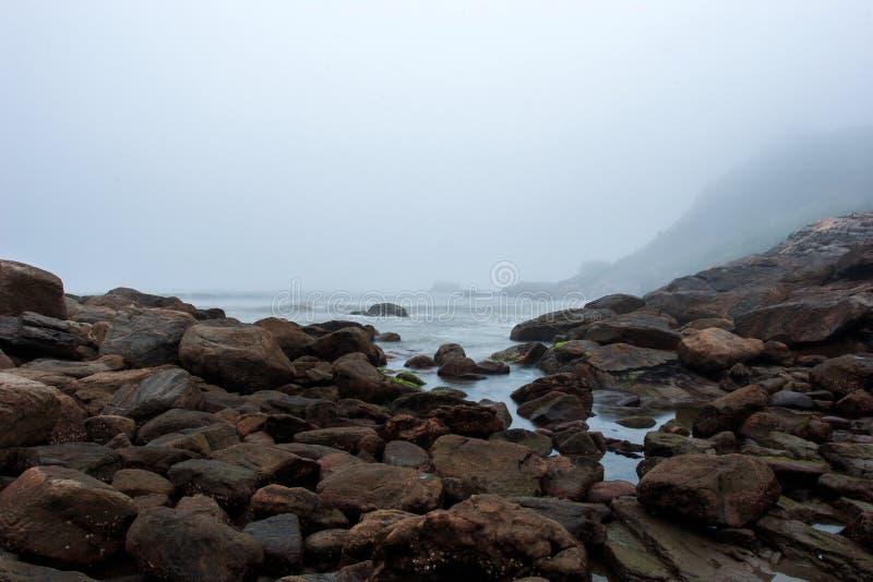 Plage brumeuse avec des roches et brume à la tombée de la nuit photo stock