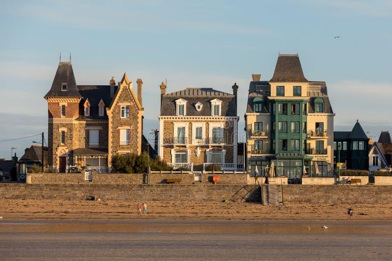 Plage dans le soleil égalisant et bâtiments le long de la promenade de bord de mer dans Saint Malo Brittany, France photo libre de droits