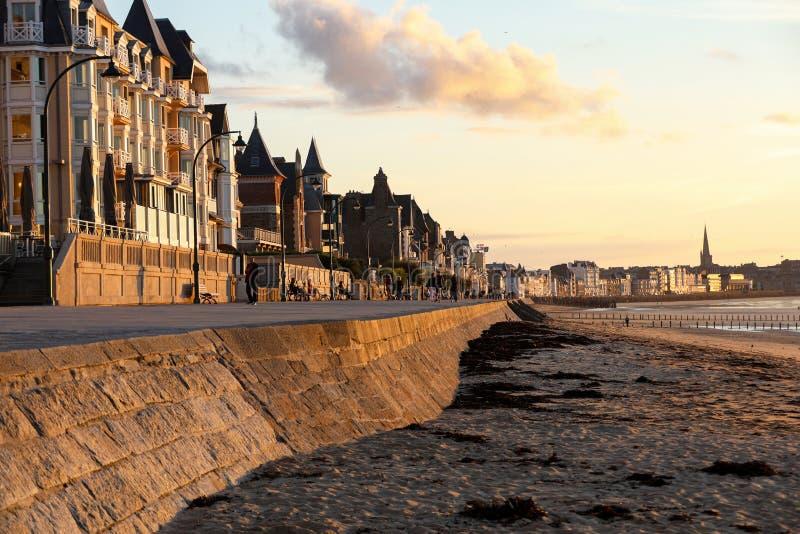 Plage dans le soleil égalisant et bâtiments le long de la promenade de bord de mer dans Saint Malo Brittany, France photos stock