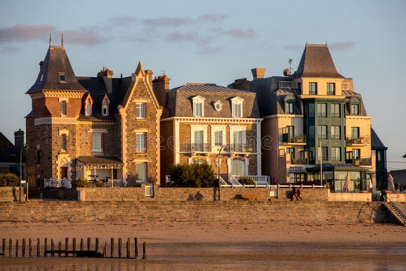 Plage dans le soleil égalisant et bâtiments le long de la promenade de bord de mer dans Saint Malo Brittany, France images stock