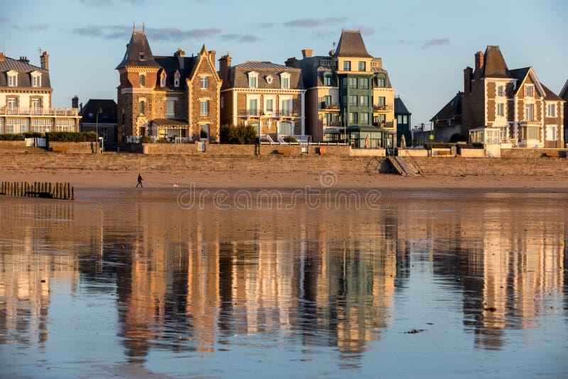 Plage dans le soleil égalisant et bâtiments le long de la promenade de bord de mer dans Saint Malo Brittany, France images libres de droits