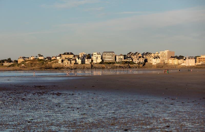 Plage dans le soleil ?galisant et b?timents le long de la promenade de bord de mer dans Saint Malo Brittany, France image libre de droits