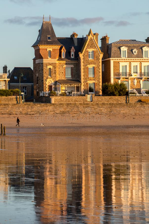 Plage dans le soleil ?galisant et b?timents le long de la promenade de bord de mer dans Saint Malo Brittany, France image stock