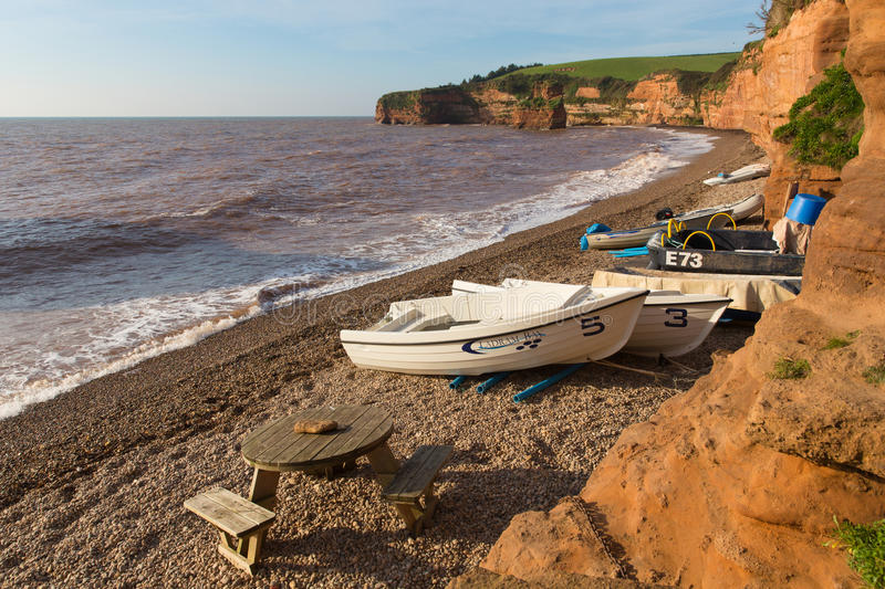Plage de baie de Ladram Devon England R-U avec la côte jurassique de roche de grès rouge de bateaux image stock