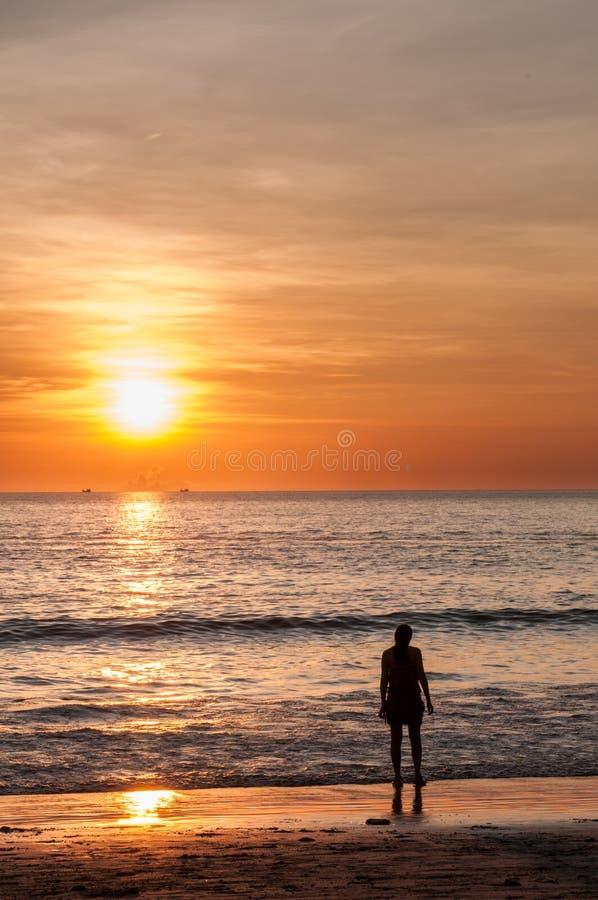 Plage de coucher du soleil avec une jeune femme image stock
