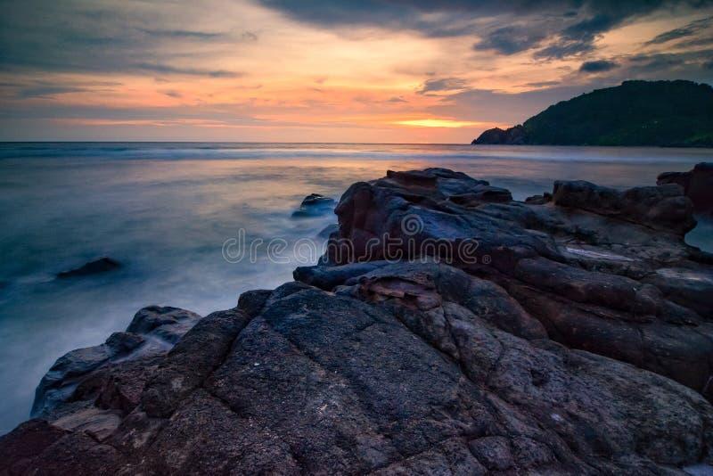 Plage de coucher du soleil et la roche images stock