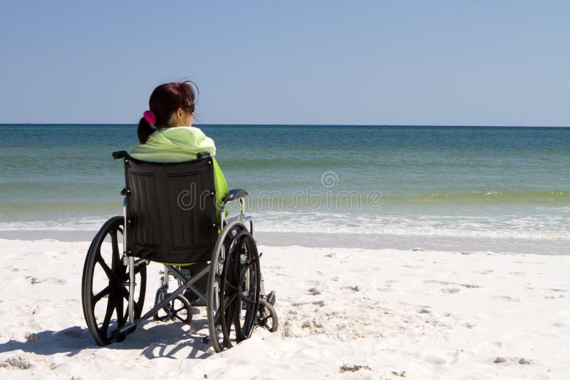 Plage de fauteuil roulant de femme images stock