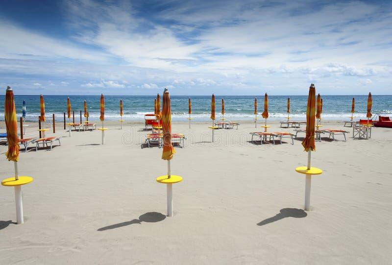 Plage de Laigueglia avec les parasols fermés image stock