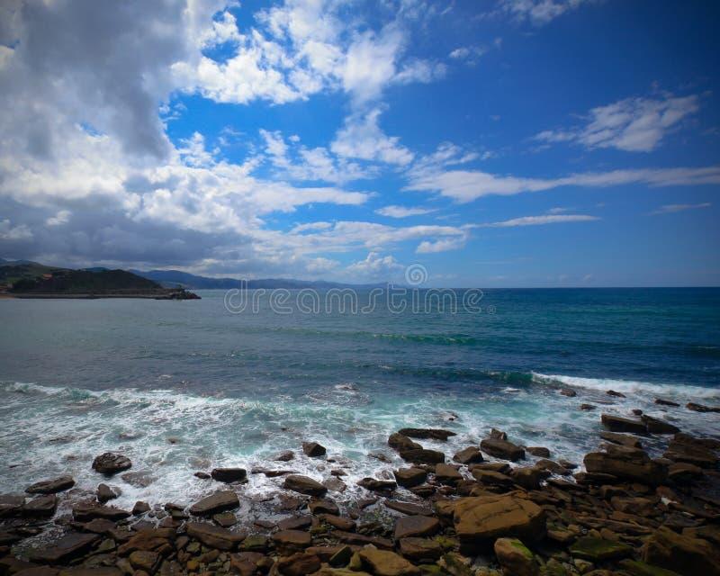 Plage de mer de caillou avec des pierres, ciel nuageux photo stock